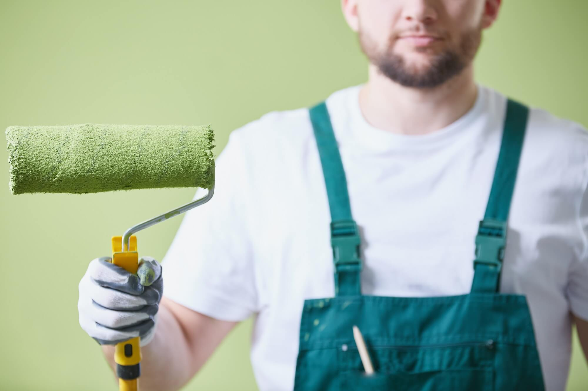 Man holding green paint roller prepared to paint the room