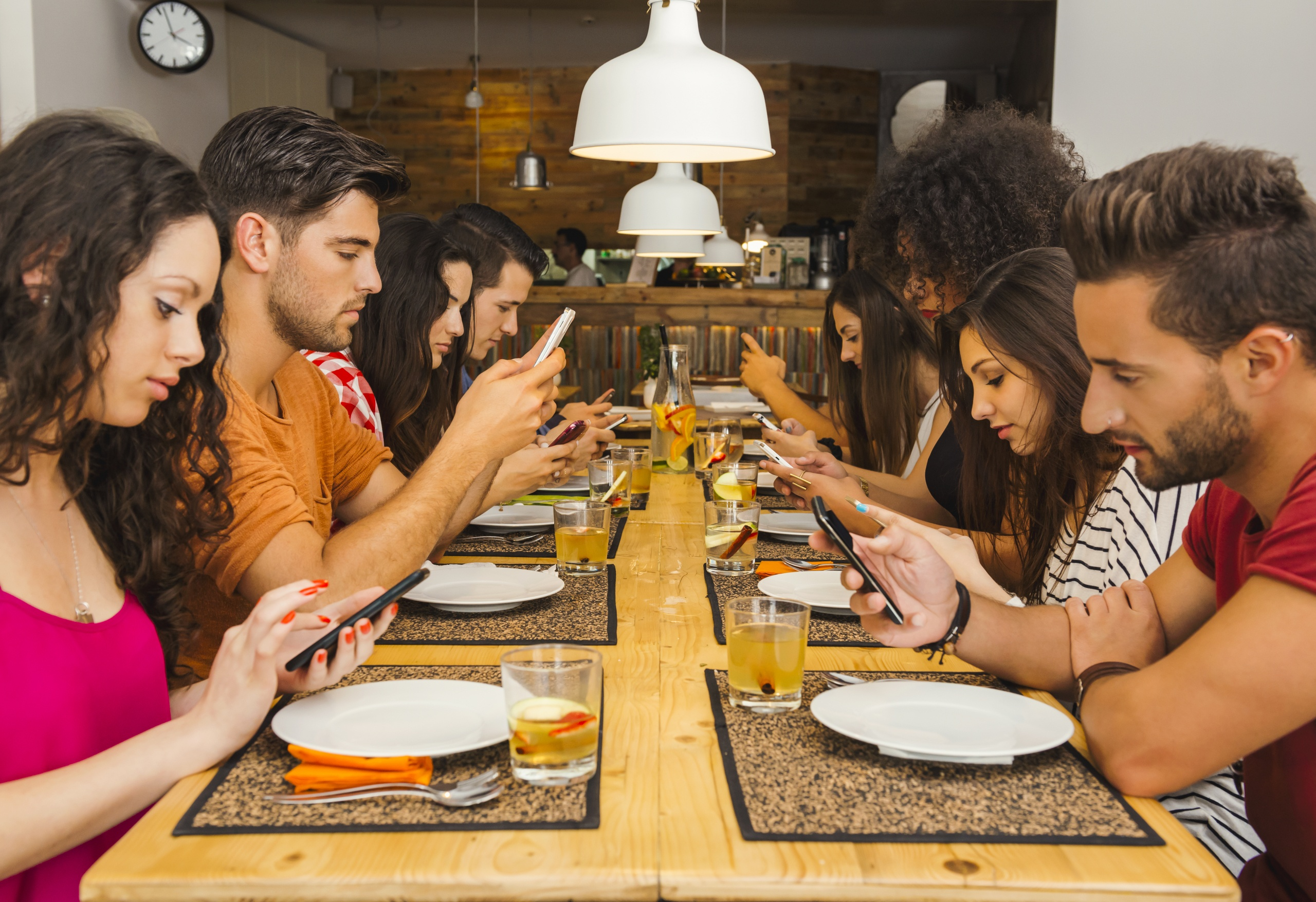 Group of friends at a restaurant with all people on the table occupied with Smartphones