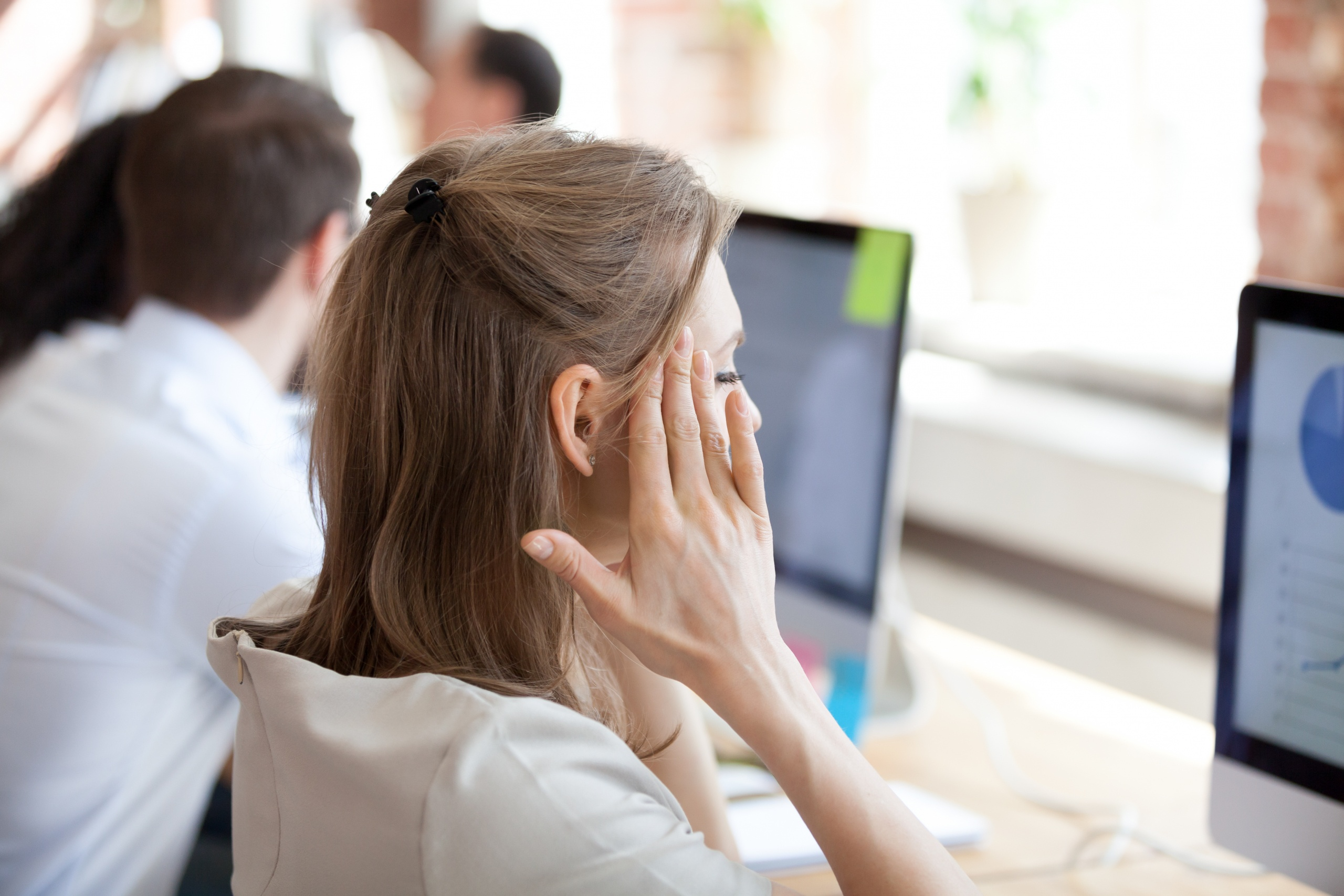 Stressed female employee massaging temples suffering from headache working too long at computer