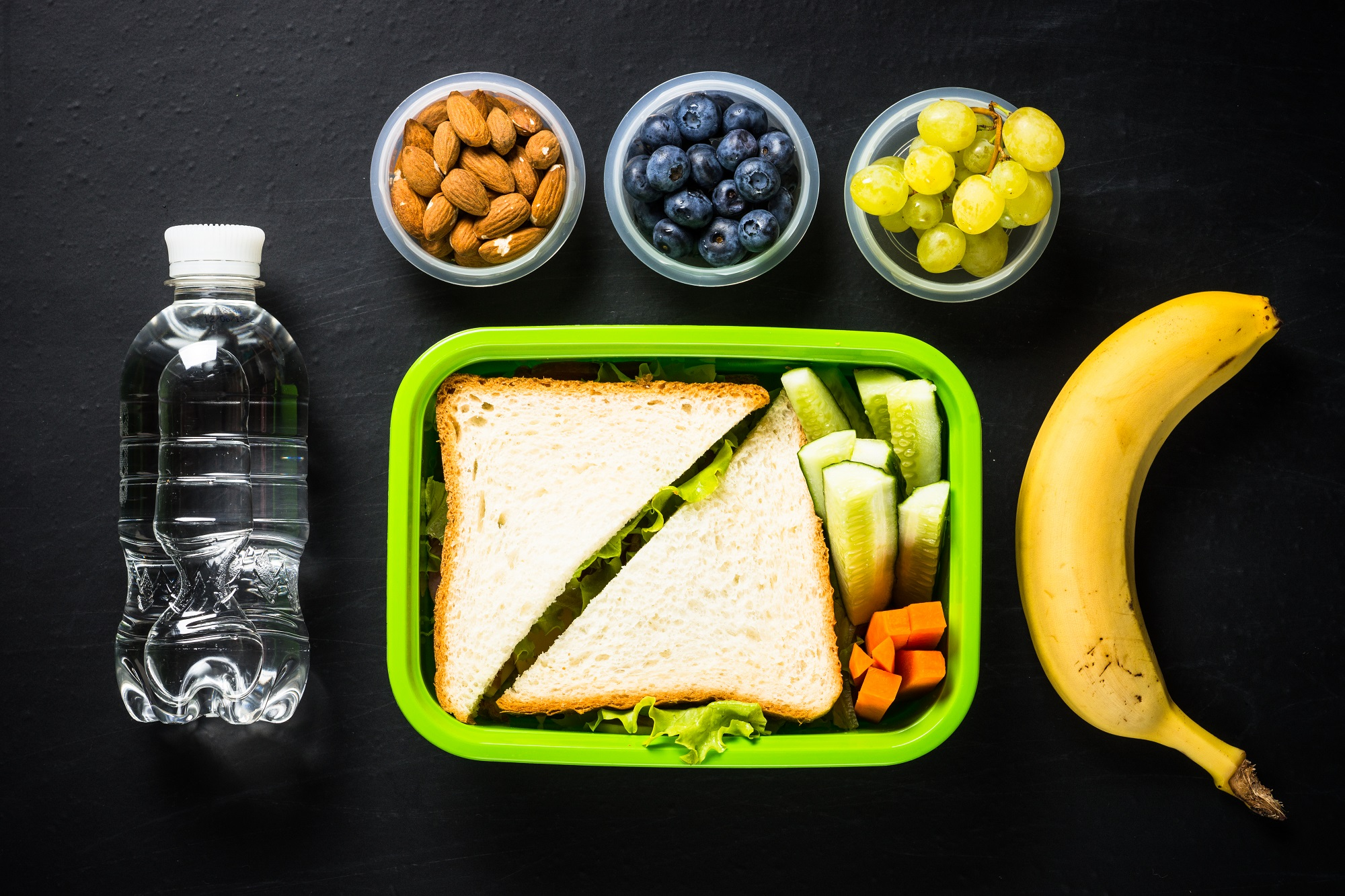 sandwich, vegetables, banana, water, nuts, and berries