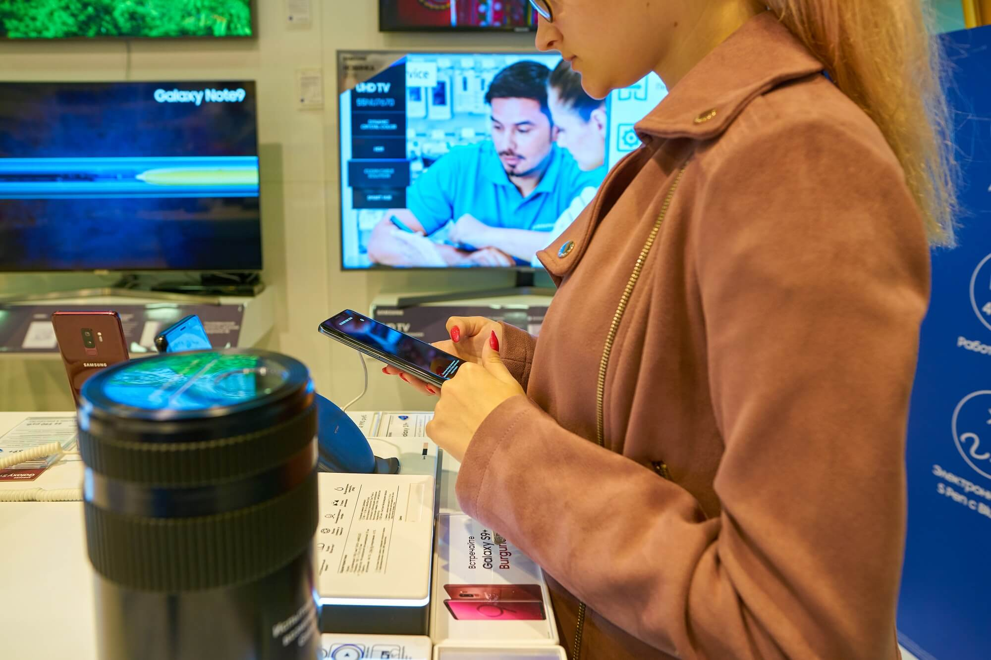 woman hold smartphone at Samsung store