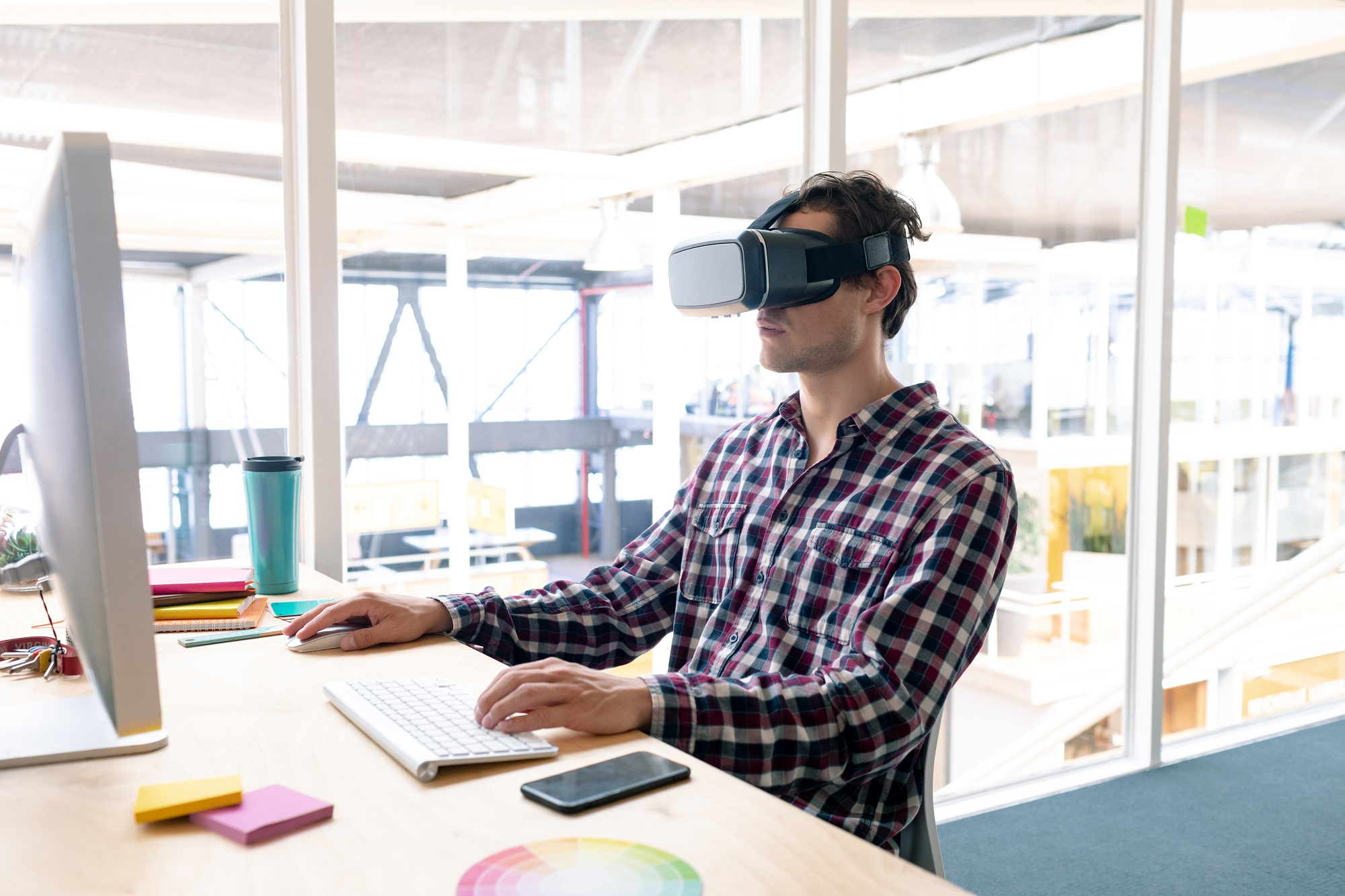 male employee using virtual reality headset while working on computer at a desk in the office