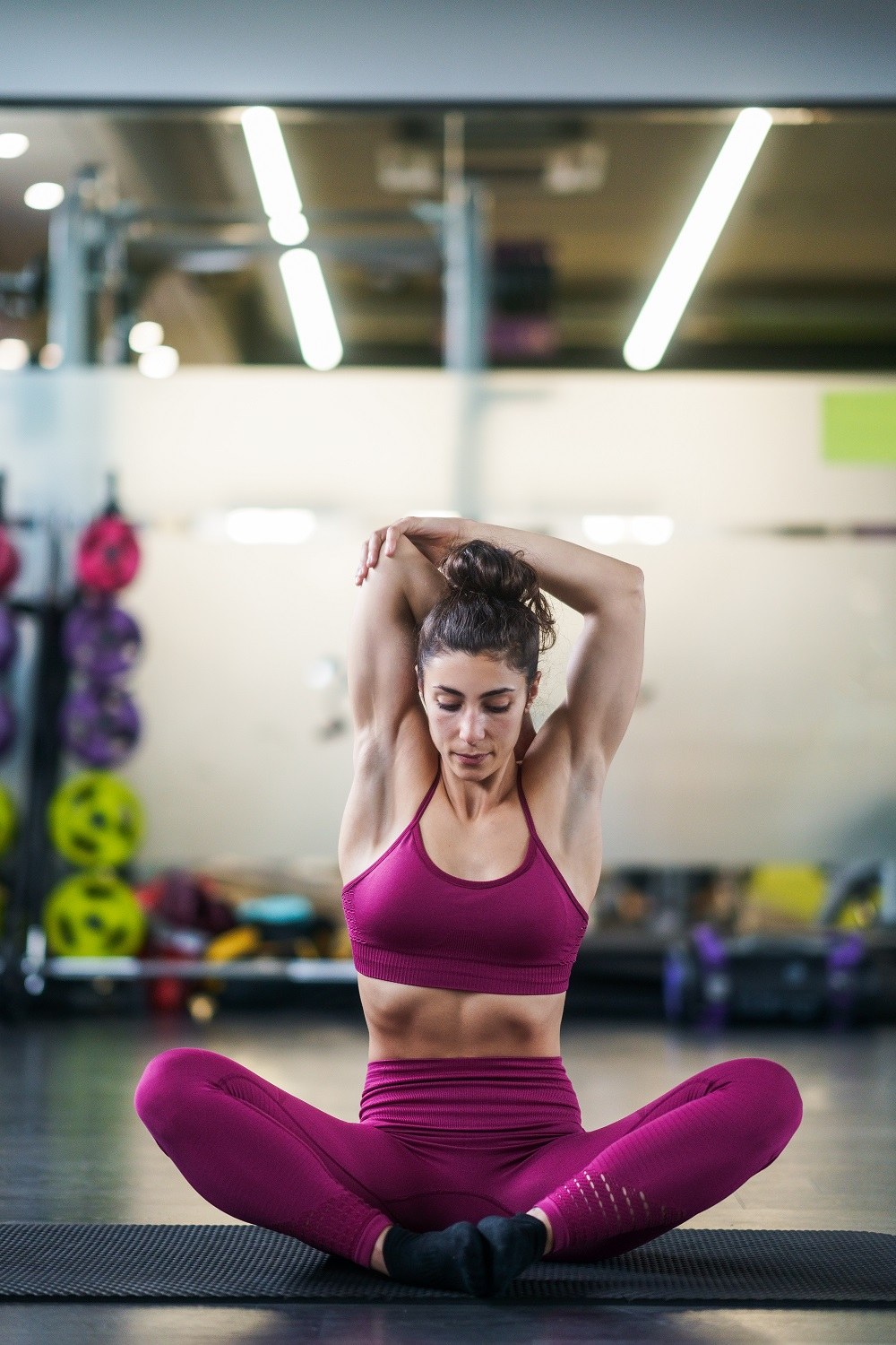 Young woman Doing Stretching Exercises on a yoga mat at the Gym
