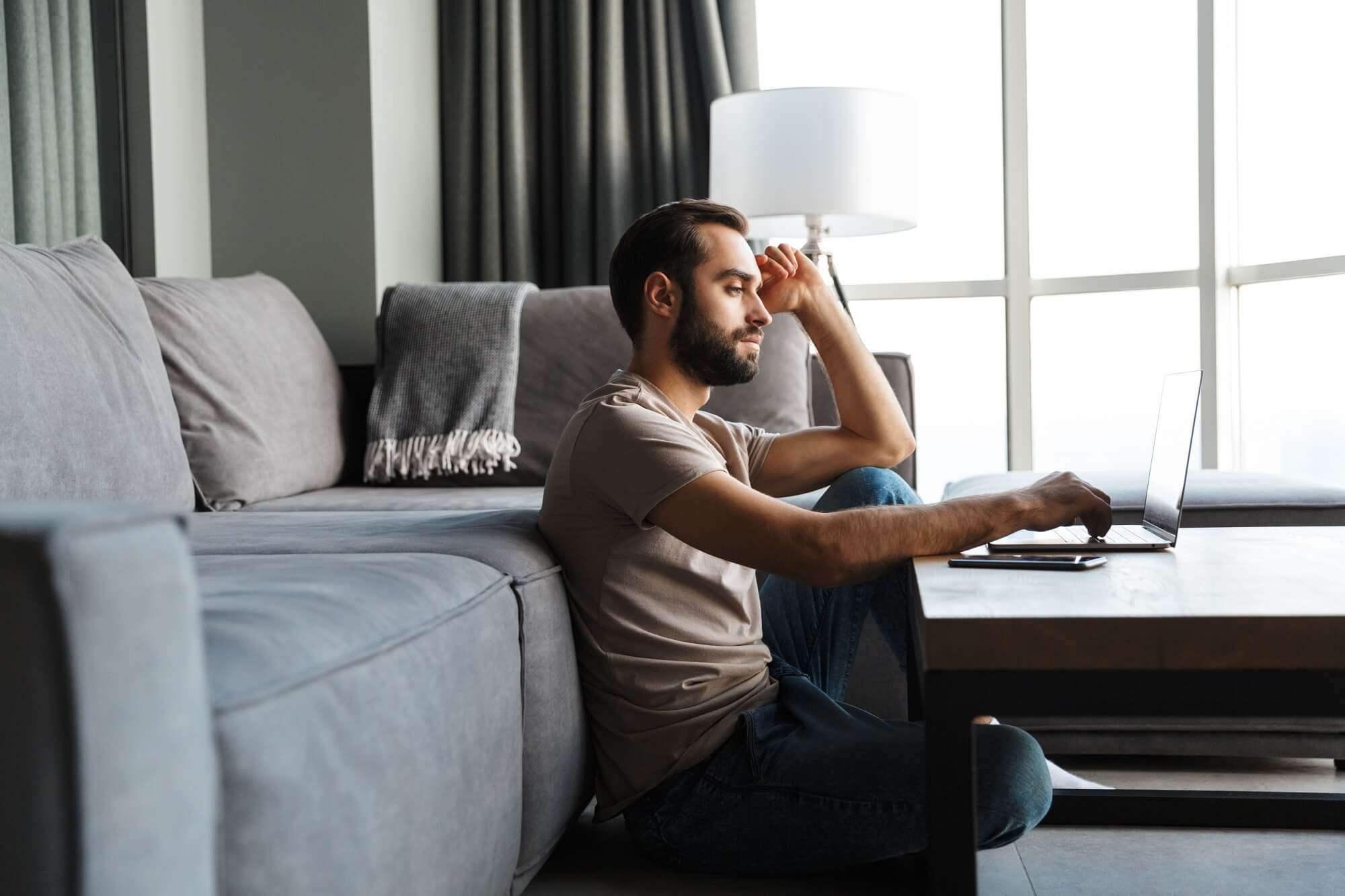 young man indoors at home using laptop computer.