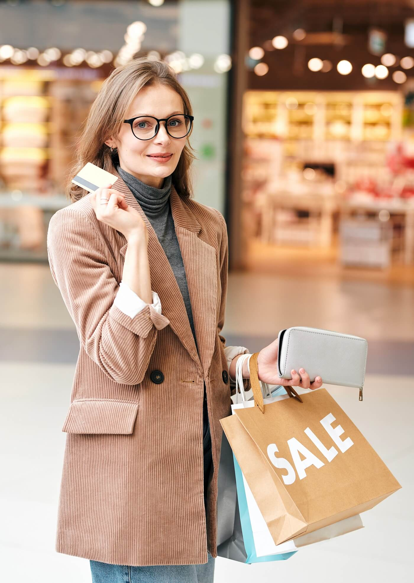 young woman standing with shopping bags