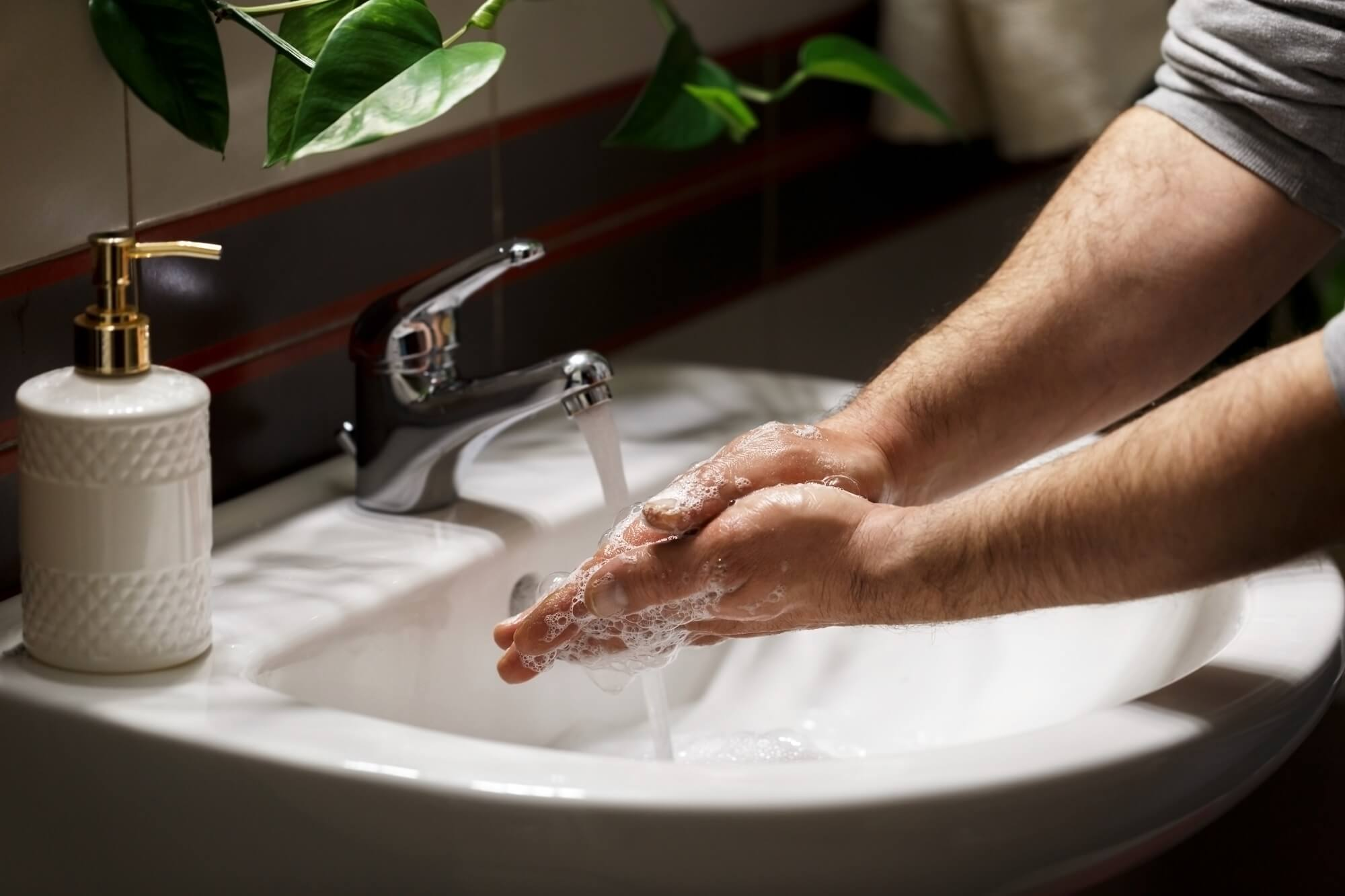 Man washing hands with soap under the fauset in the modern bathroom