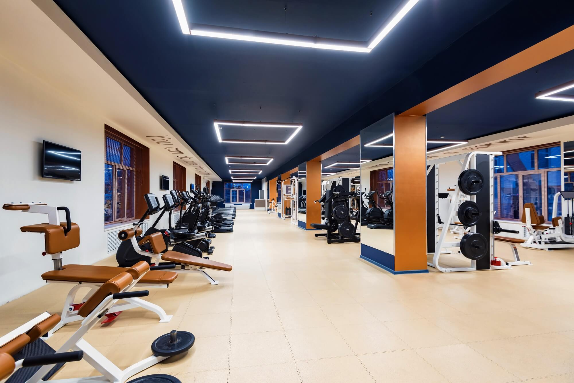 Interior with several modern fitness machines in gym