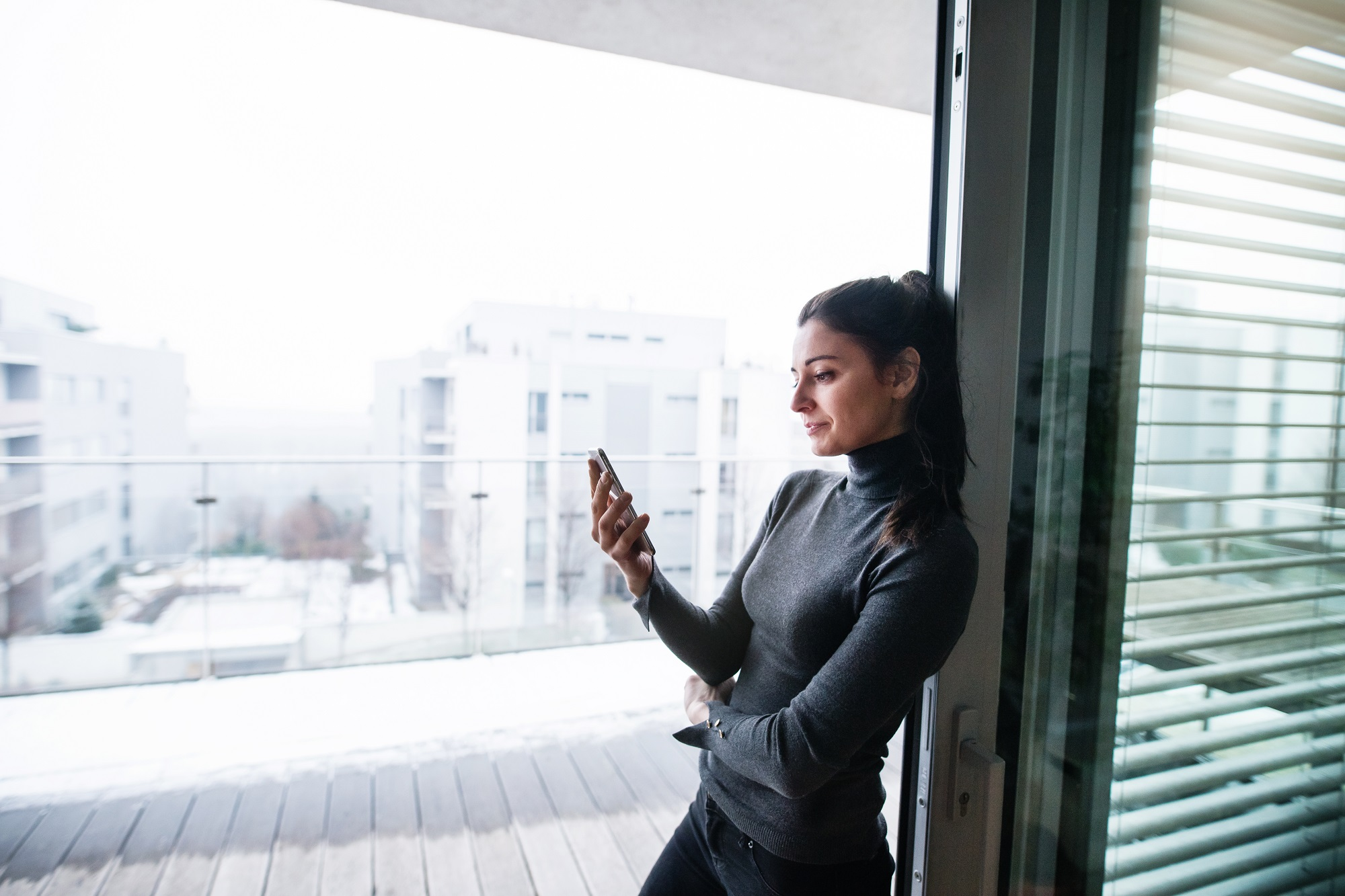 A woman standing by the window, holding smartphone.