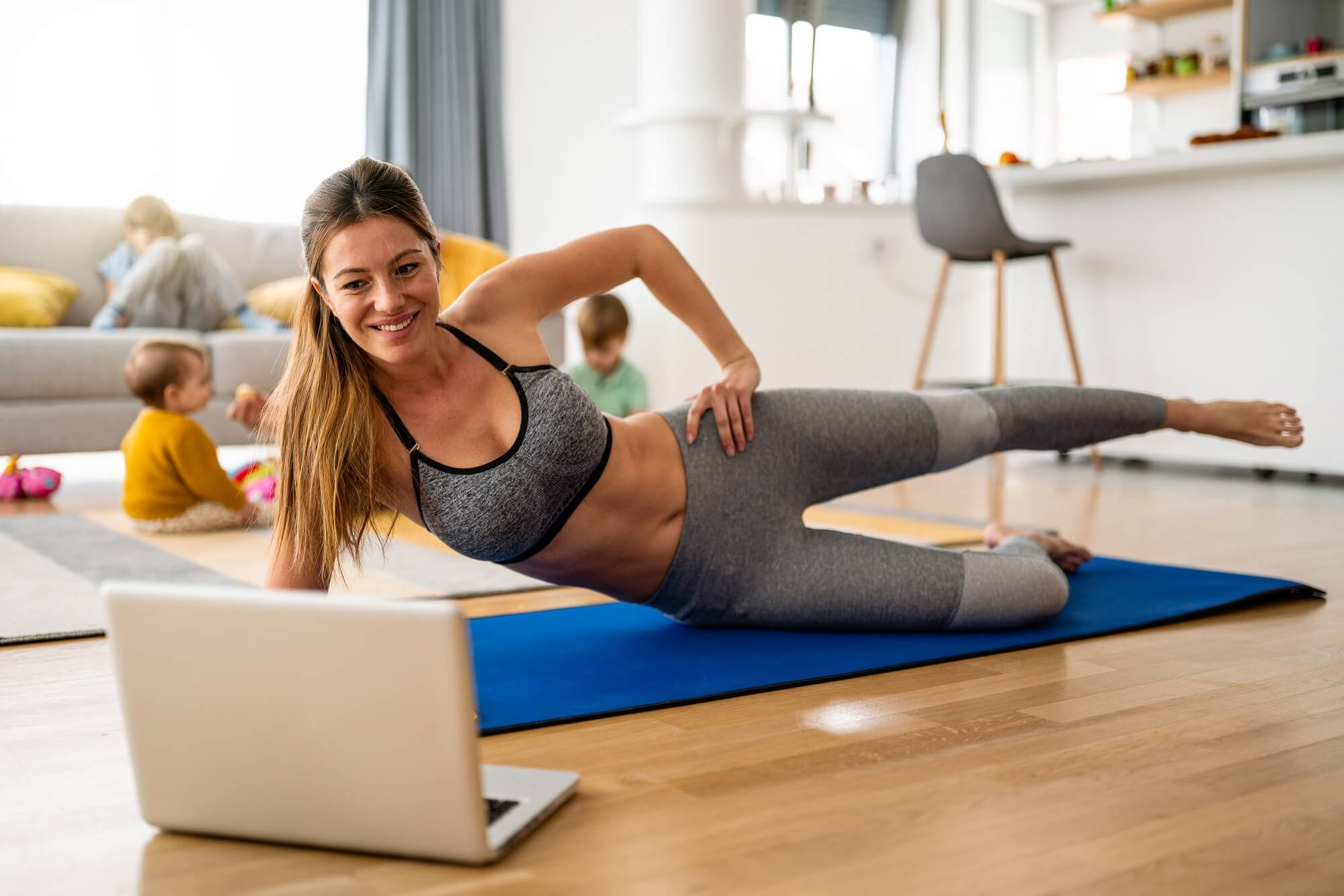 Young fit woman, mother exercising at home in living room