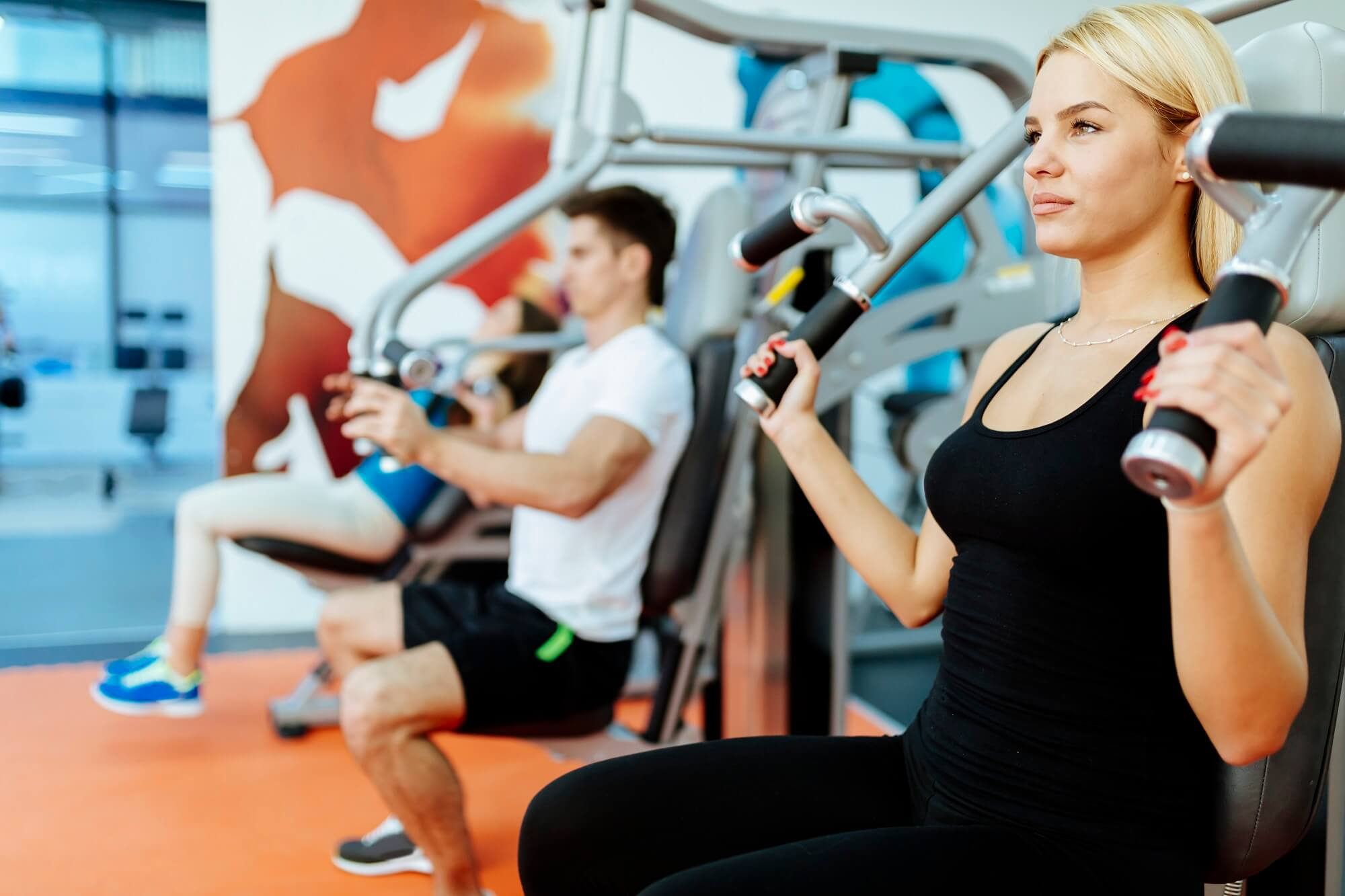 People exercising in gym on various machines