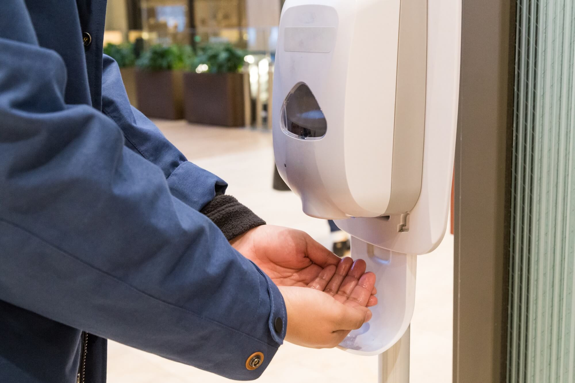 A person cleaning hand with anti-bacterial hand disinfectant sanitizer dispenser at work