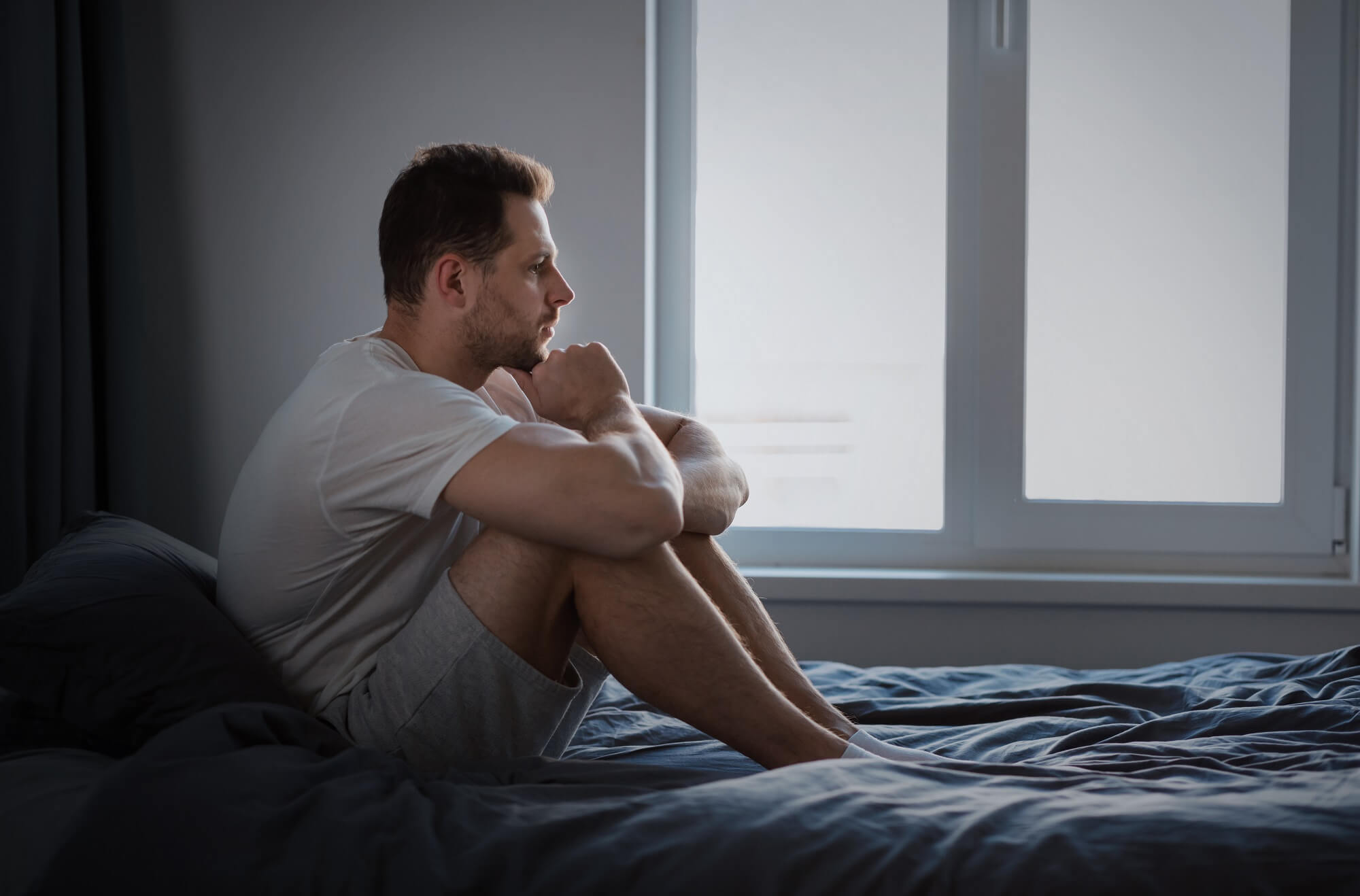 Depressed Man Thinking About Problems Sitting In Bed Indoors