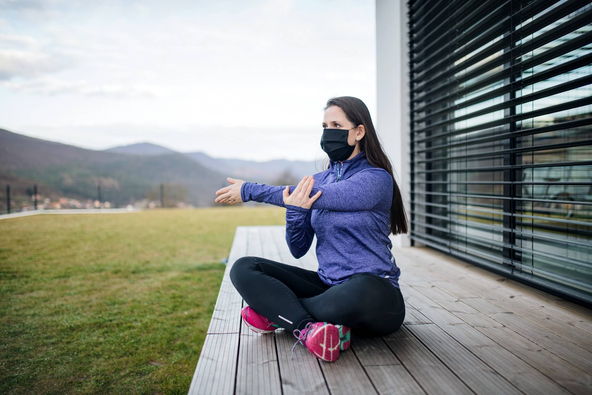Woman with face masks doing exercise outdoors at home