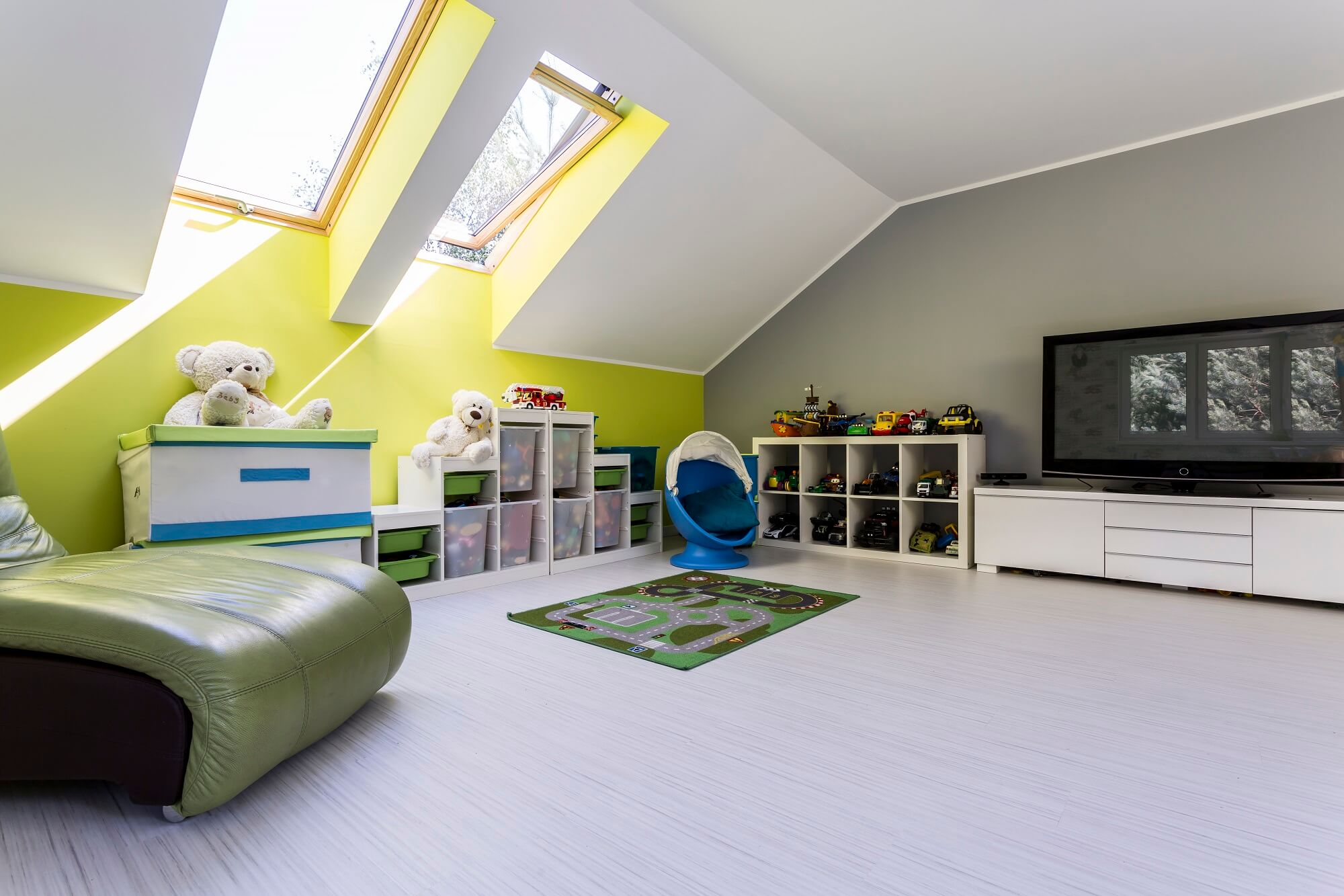 Child room at the attic with TV set, bed, chest of drawers and toys