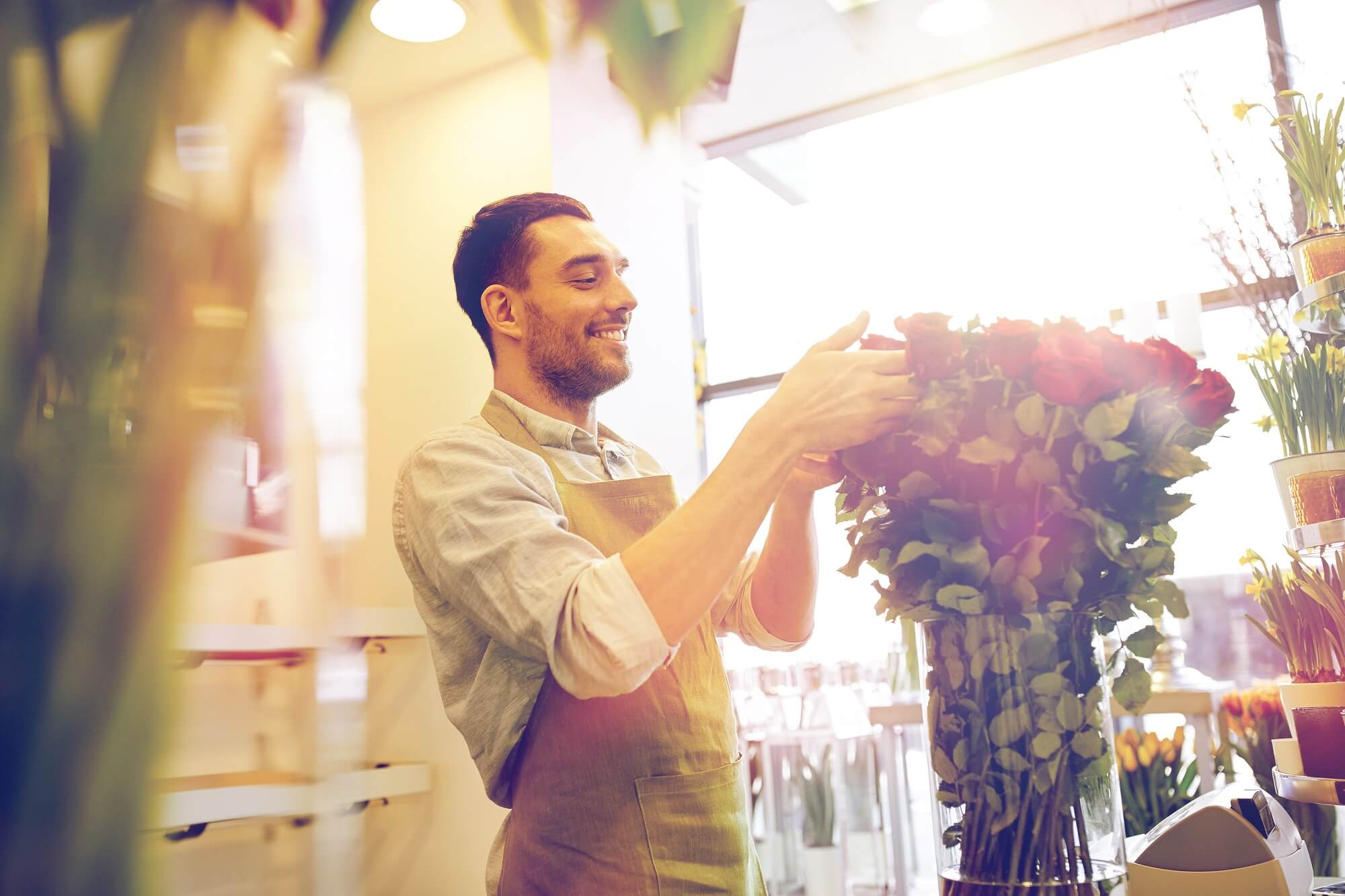 happy smiling florist with red roses at flower shop