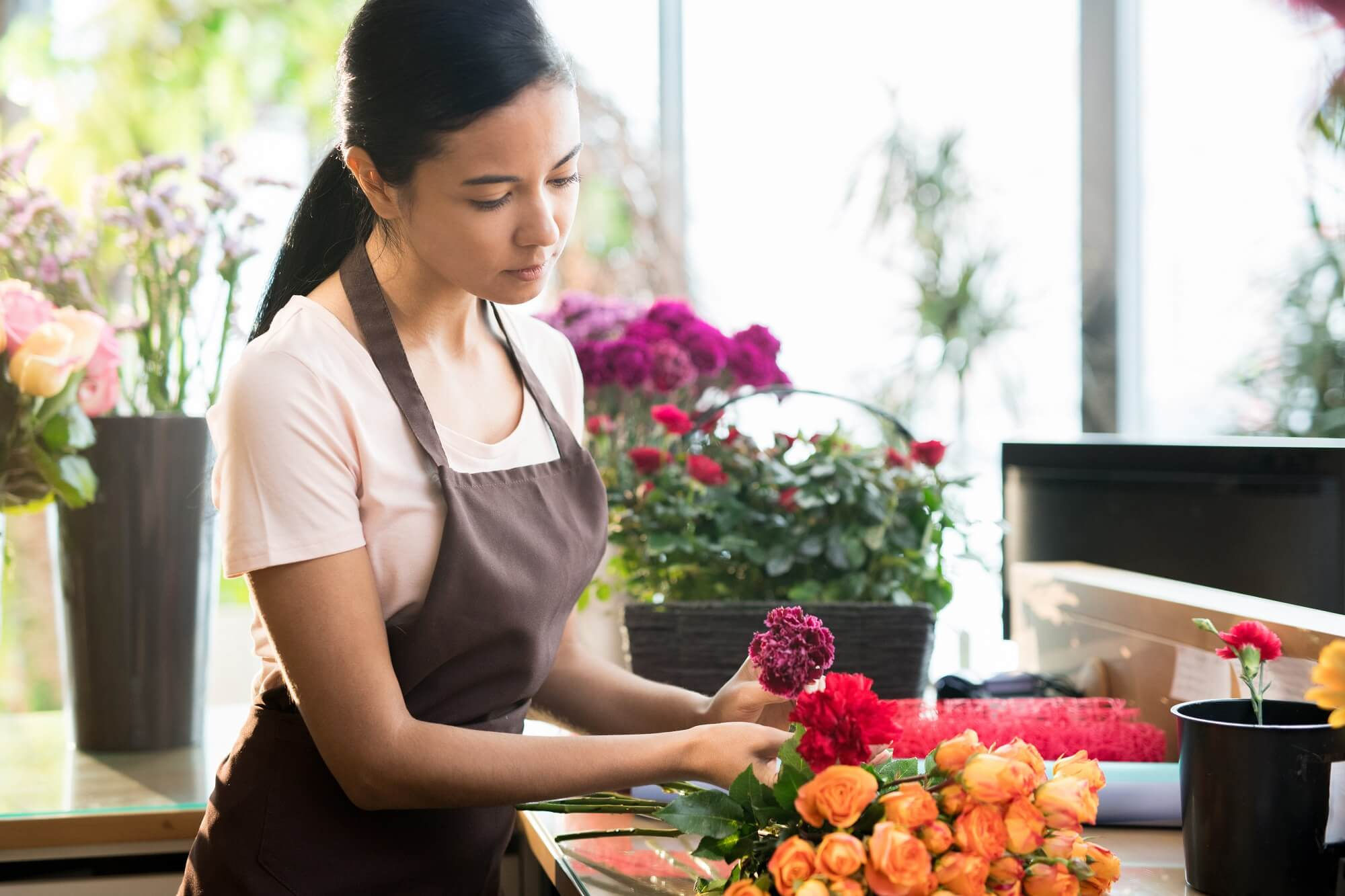Young brunette florist in workwear sorting fresh roses and carnations on table during work in shop