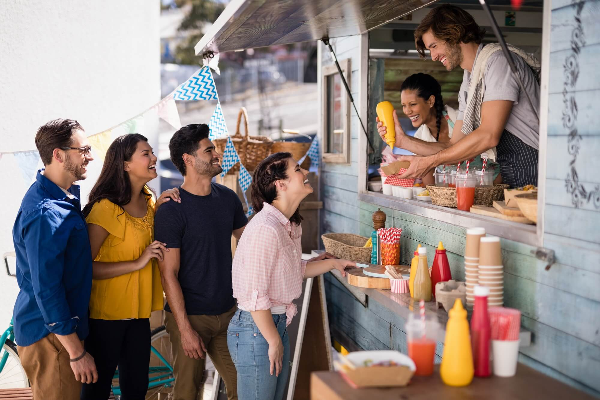 Smiling waiter serving customers at counter in food truck