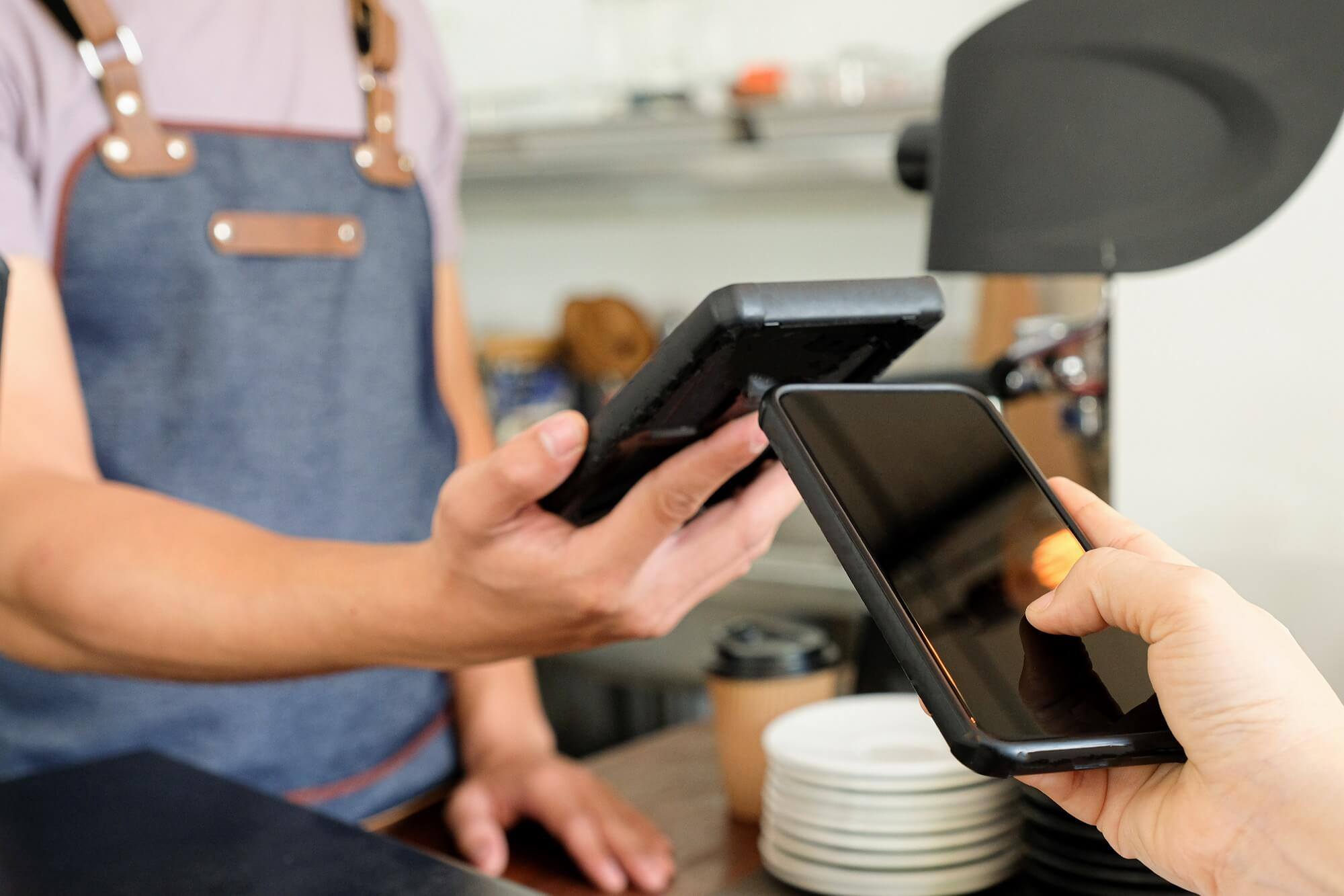 Customer and business owner are holding a smartphone to pay via the App.