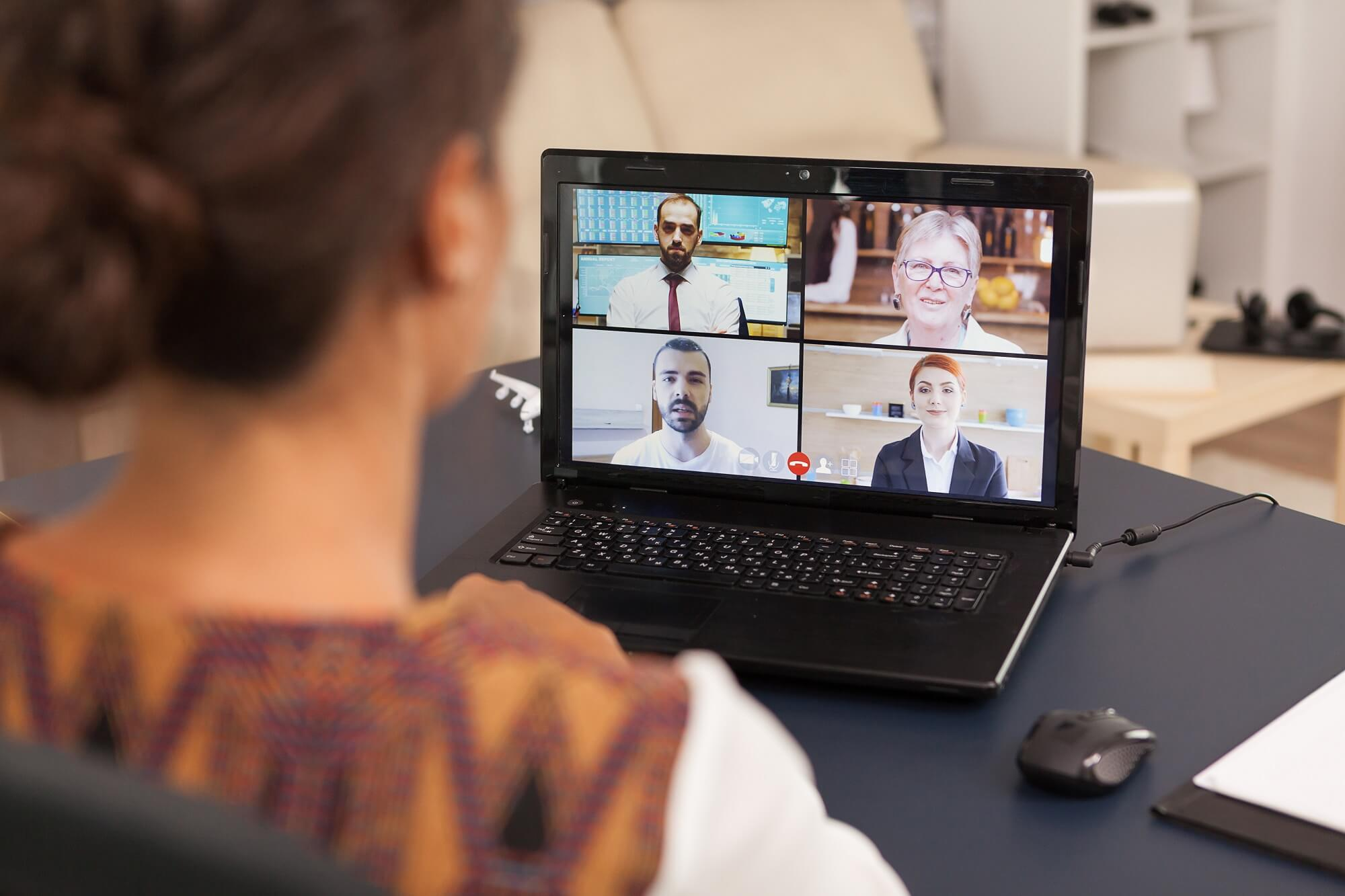 Woman talking with work colleagues on video call using computer from home.