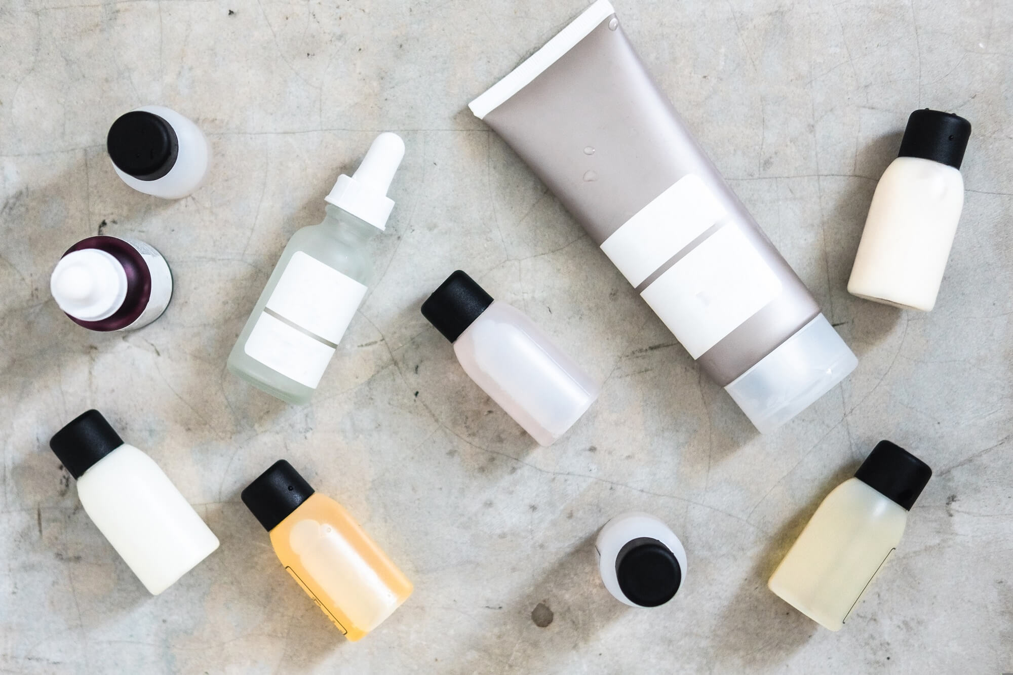 Bottles and tubes with salon cosmetic products from above on concrete table
