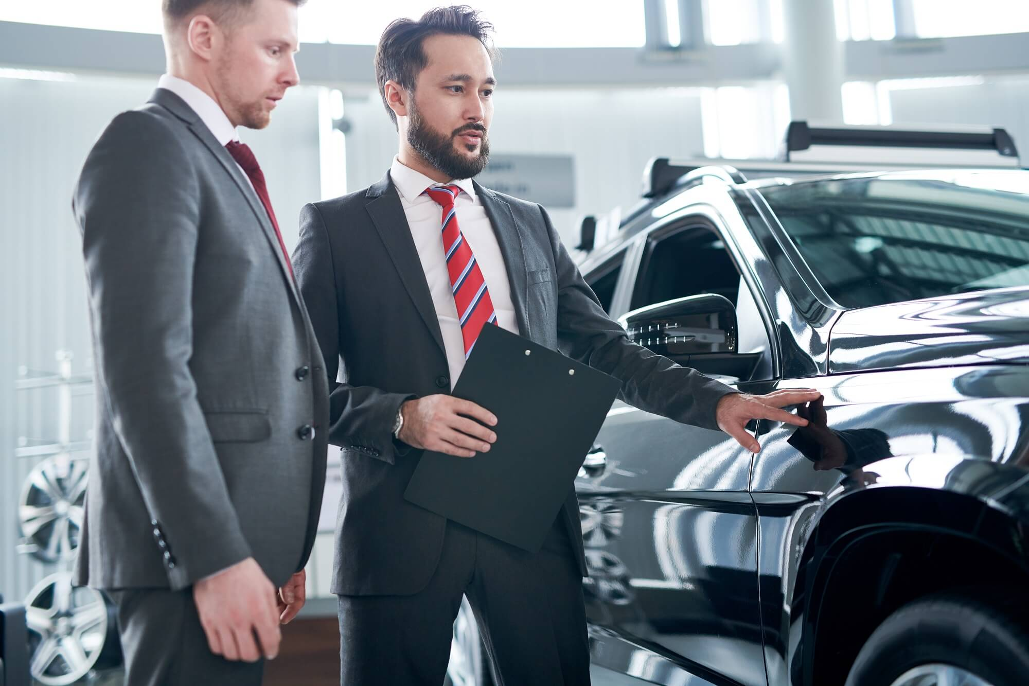 Professional sales person showing car to customer