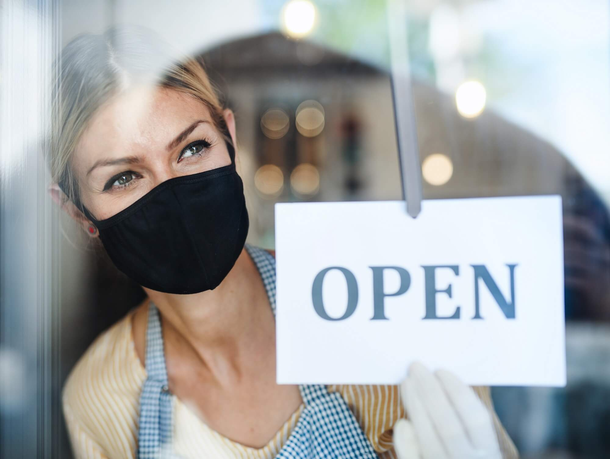 shop owner welcoming customers safely for cyber monday deals