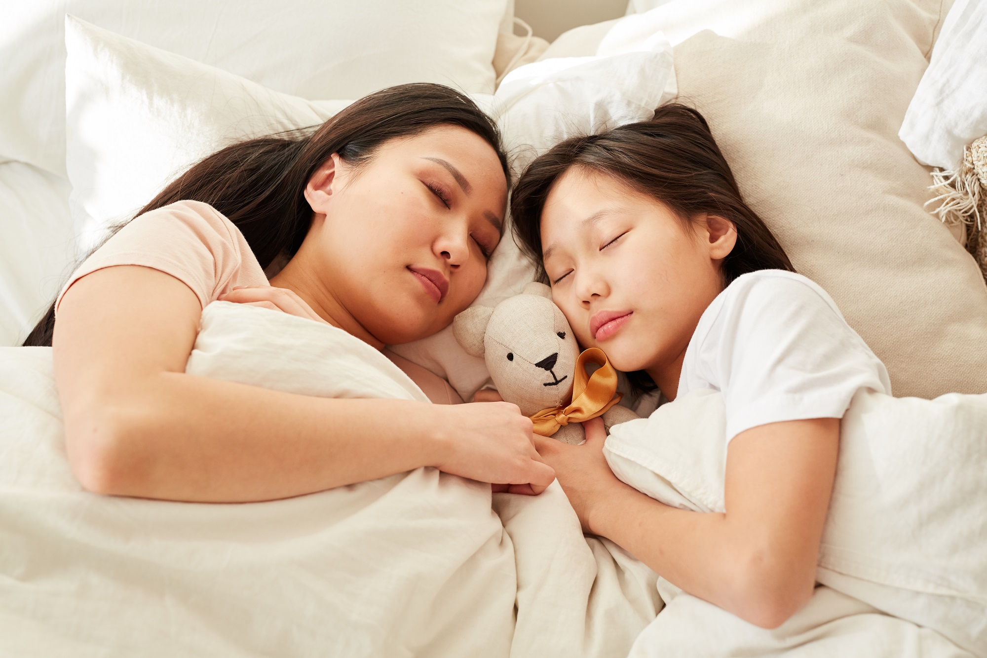 Asian mother sleeping together with her daughter in the bed in the bedroom