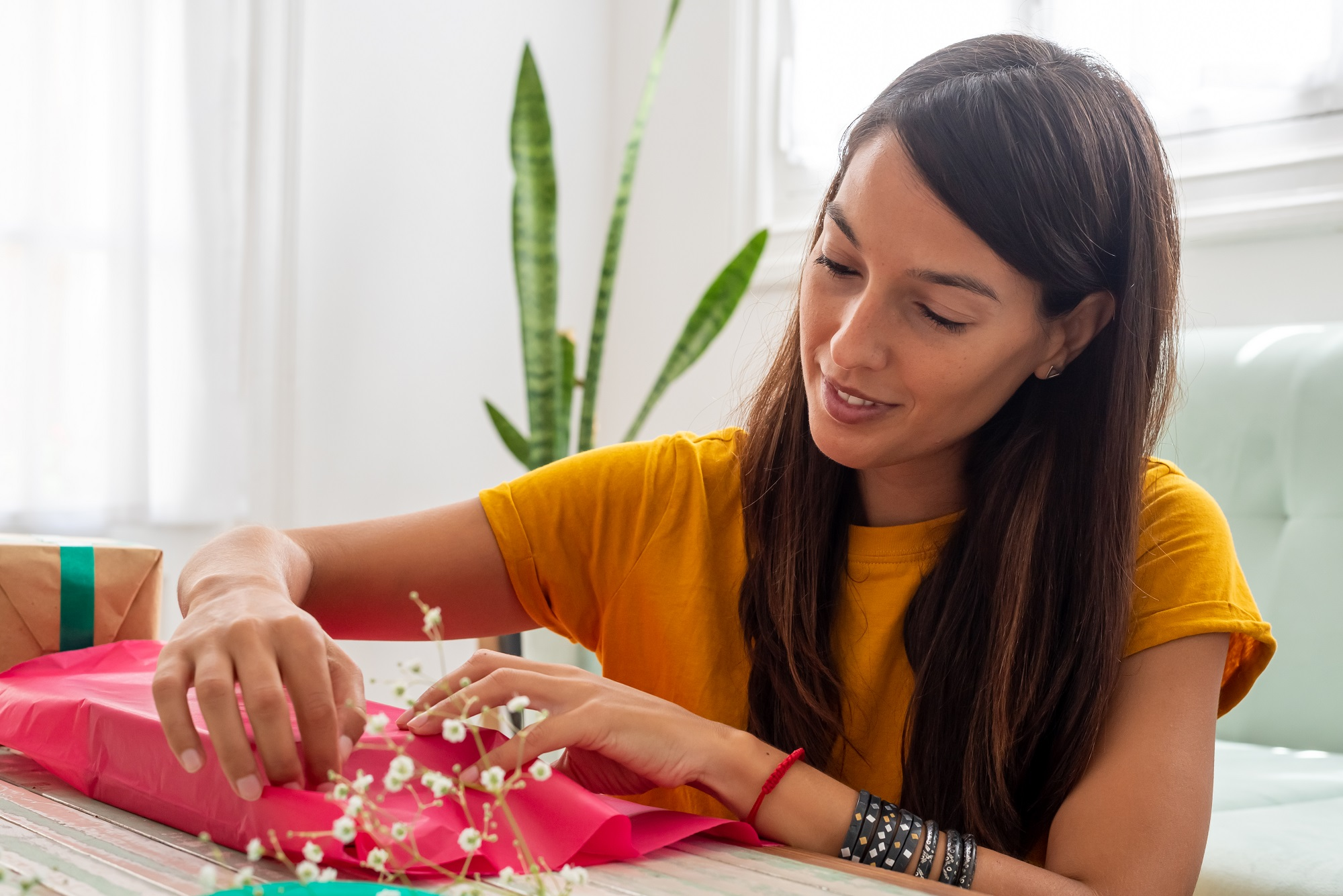 Woman wrapping diy beauty hamper  on the table at home