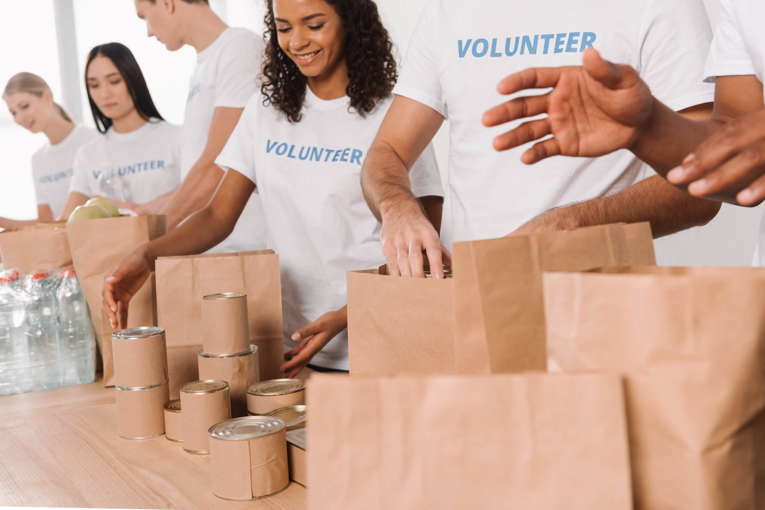 cropped shot of volunteers putting food and drinks into paper bags for charity
