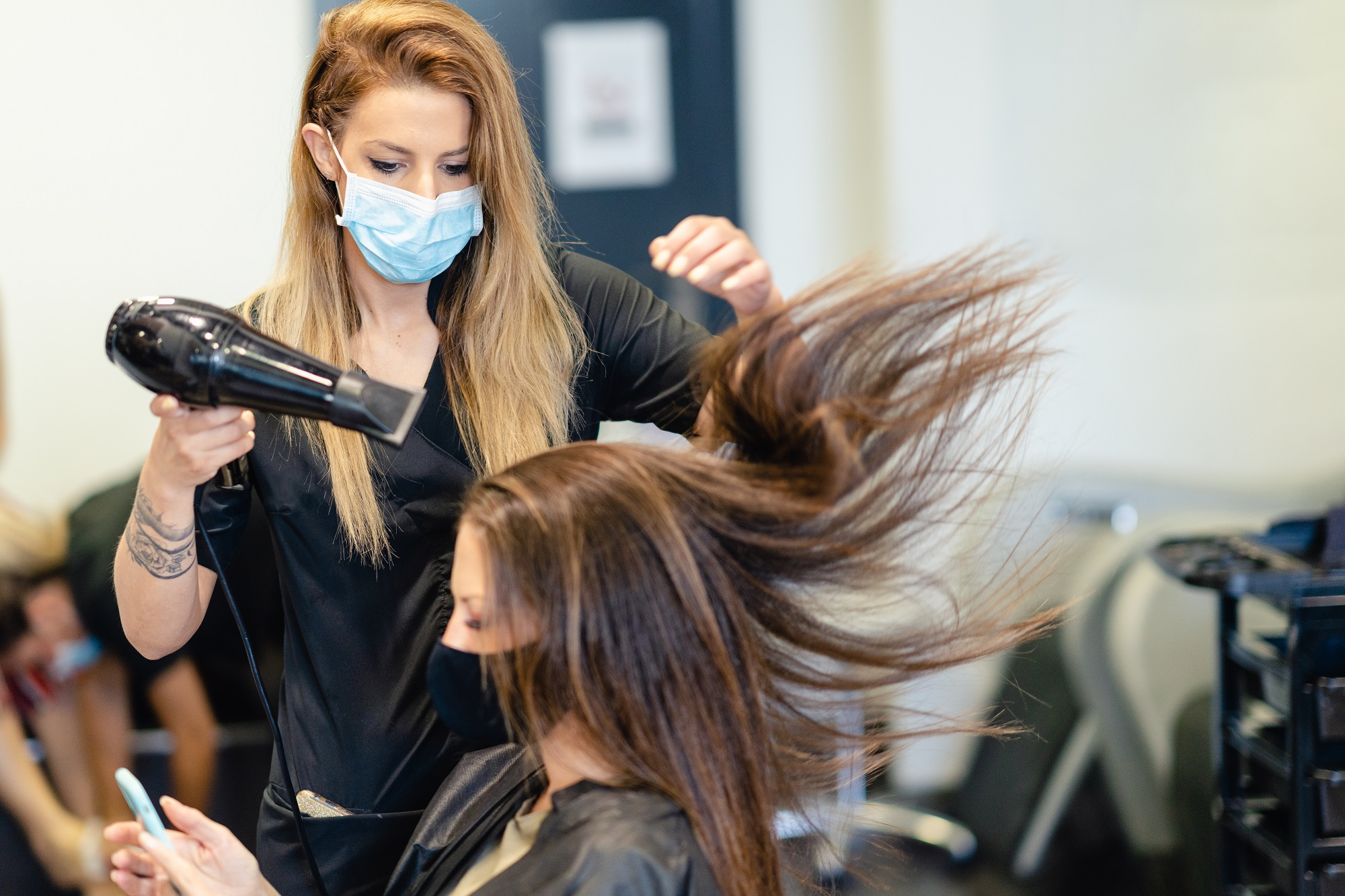 Female hairdresser drying her client's hair with a hairdryer, wearing protective masks