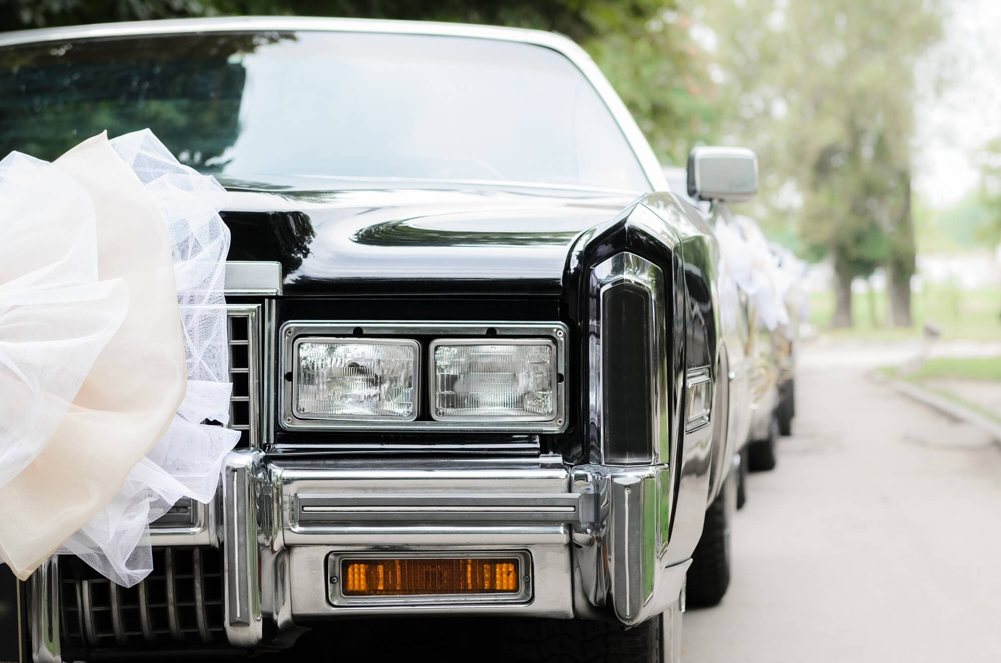 black vintage wedding car with white bow
