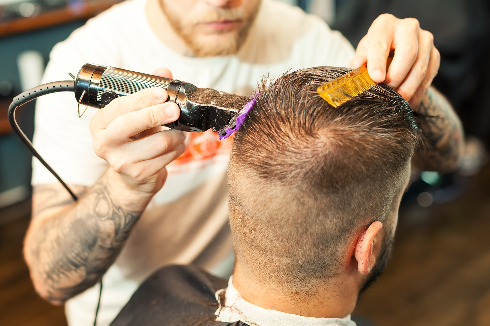 young man having hair dress, barber working with hair clipper at  local mobile hairdresser shop