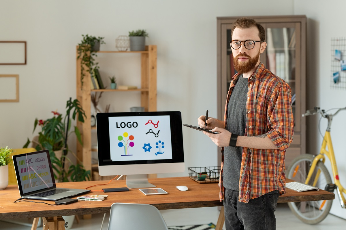 designer working on brand building with beard drawing on digitizer table