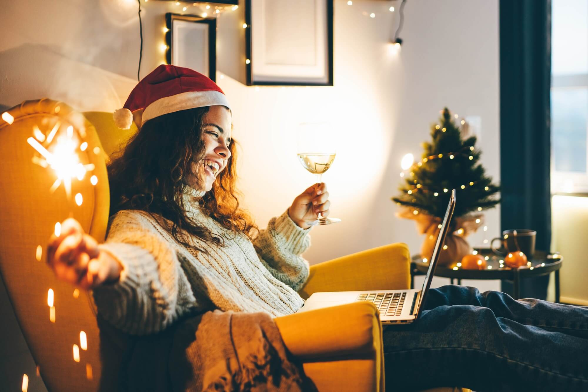 Happy young woman wearing Santa hat, drinking champagne, talking with friends on video call celebrate xmas