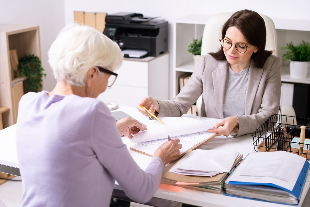 financial adviser working with senior woman giving pension advisers