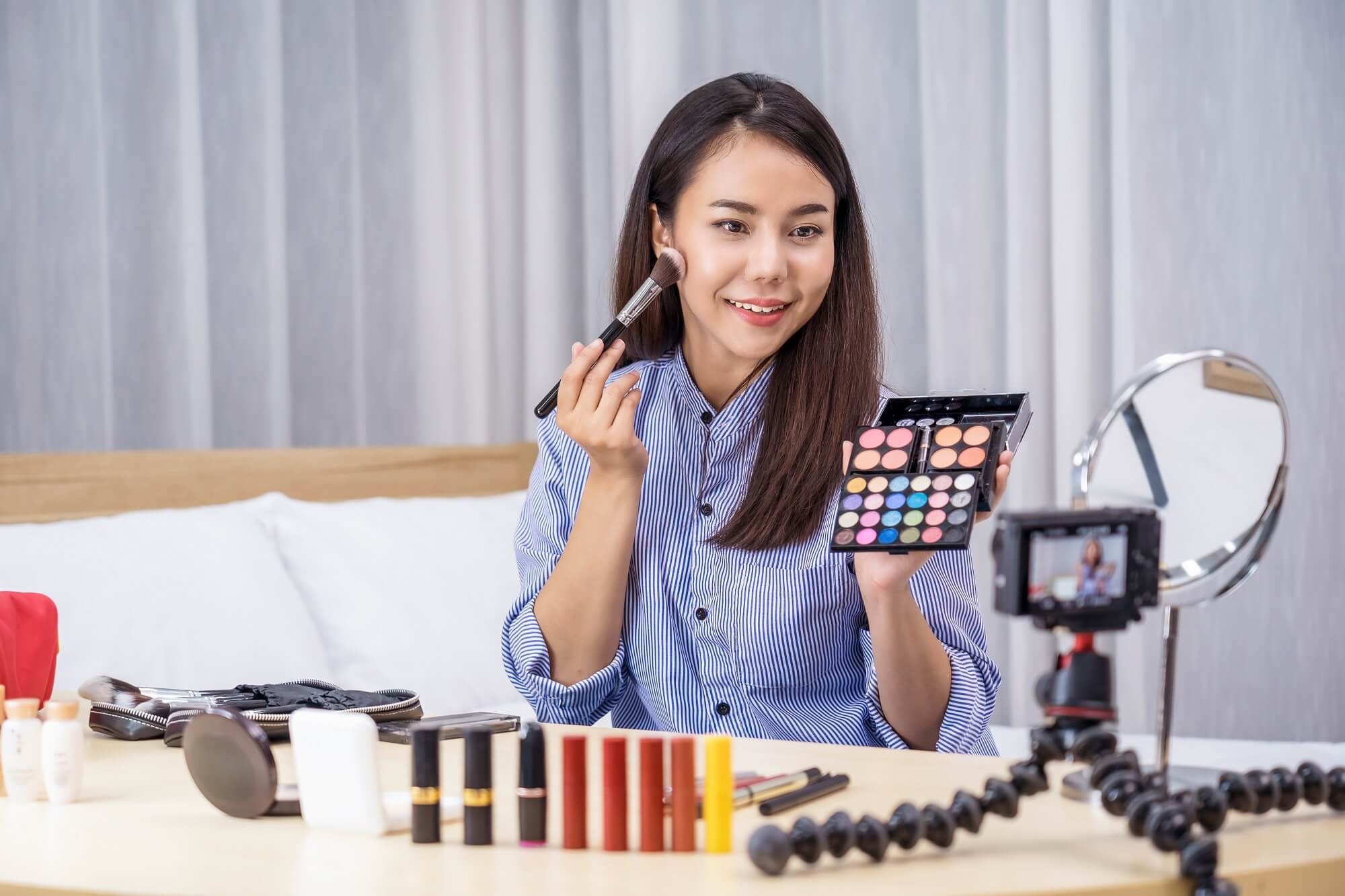 beauty vlogger showing makeup online tutorial services on social network media via video recording