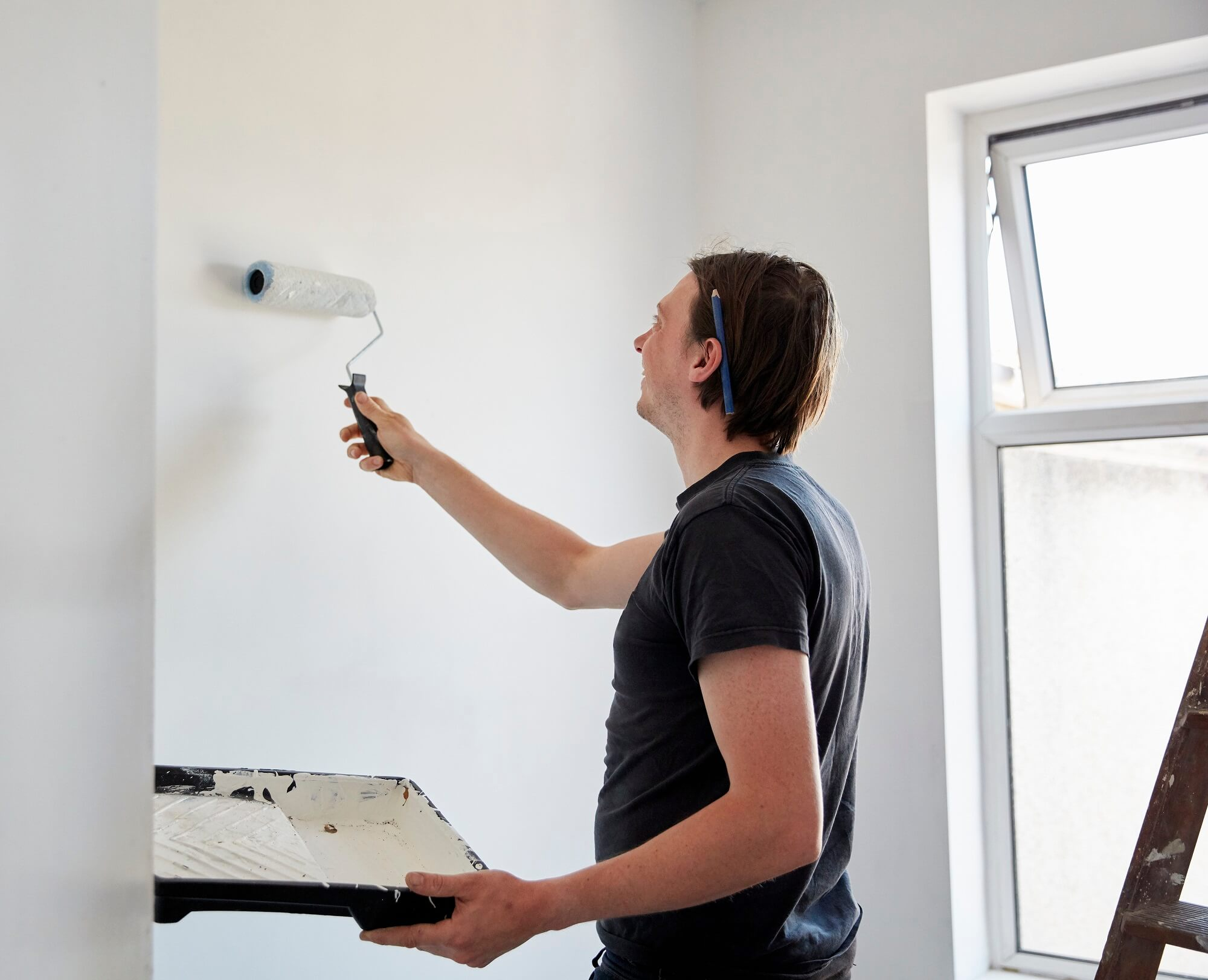 A painter using a paint roller and holding a paint tray, decorating a room.