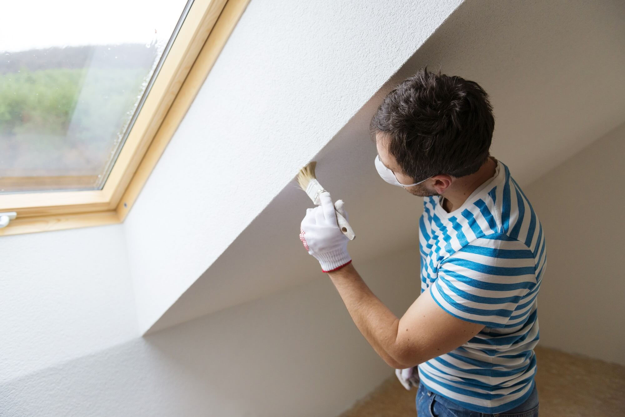 Professional painter painting the wall of a new home with a paintbrush