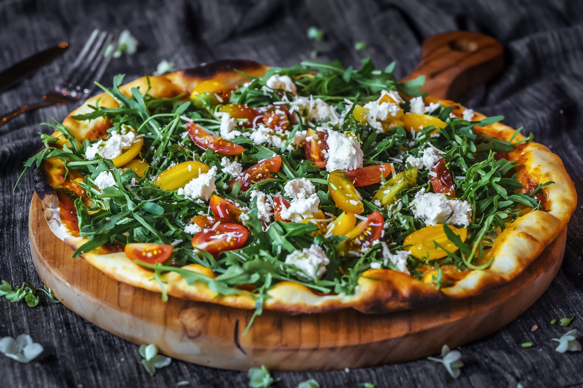 Pizza with tomatoes, feta cheese, salad and red onion for a healthy takeaway