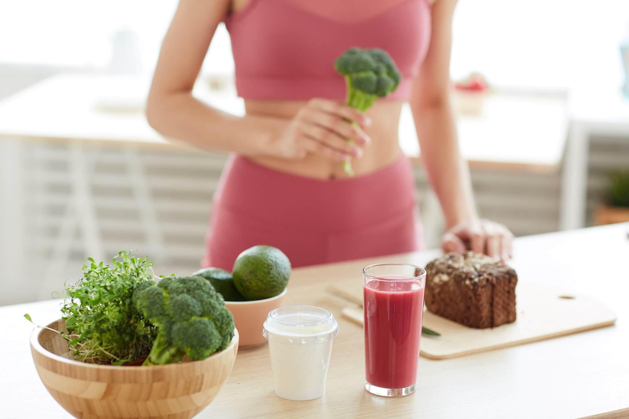 women with green vegetables and fresh juice